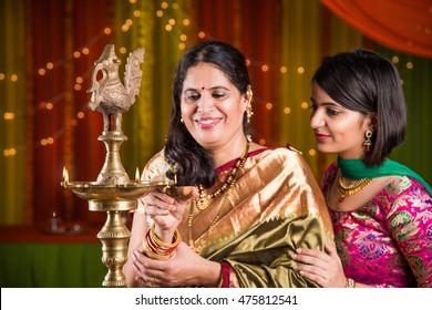 Indian woman and daughter in traditional wear lighting Diya Or Samai Lamp on ganesh festival or Diwali