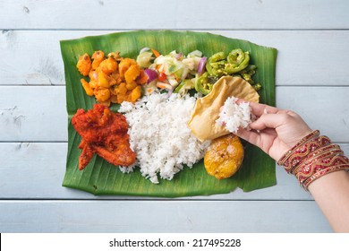 Indian woman eating banana leaf rice, overhead view on wooden dining table.