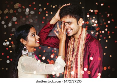 Indian woman is giving blessings to the brother by putting tika on his forehead. Both wearing traditional ethnic clothes. Focus on man's eyes