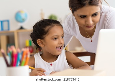 Indian woman helping young girl with laptop to do homework