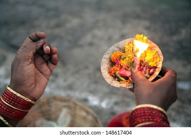 Indian woman holding candle with flowers