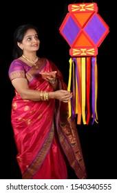 An Indian woman holding a traditional Diwali lamp adoring her Diwali lantern also called as sky lantern