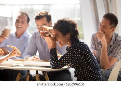 Indian woman laughing at funny joke eating pizza with diverse coworkers in office, friendly work team enjoying positive emotions and lunch together, happy colleagues staff group having fun at break - Shutterstock ID 1206996136