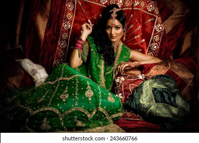 Indian woman laying in luxury ethnic interior.