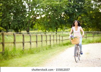 Indian Woman On Cycle Ride In Countryside