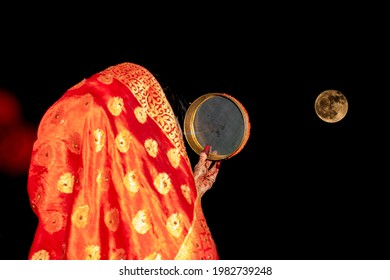 Indian Woman on Left Side Standing Back side Doing Karva Chauth Festival at night in front of Moon