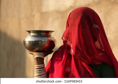 Indian woman on a market with a red veil, covering her face, her eye shimmering through the veil. She holds a silver pot in her hand. Her arm is decorated with silver bracelets