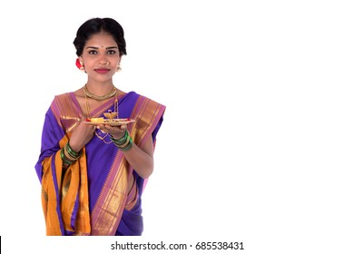 Indian woman performing worship, portrait of a beautiful young lady with pooja thali isolated on white background