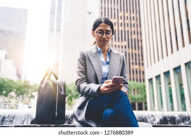 Indian woman receiving text message on smartphone while sitting on bench outdoor in city. Young female browsing LTE internet and reading article on website. Millennial people communication and network