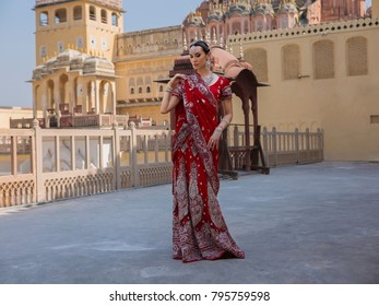 Indian Woman in Red Bridal Sari clothing with bridal oriental wedding jewelry. Beautiful Maharani. Beautiful Girl in wedding Sari. Indian Bride in oriental Palace Hawa Mahal