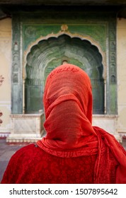 Indian Woman in red scarf looking at green gate door in City Palace of Jaipur, Rajasthan, India. Space for your text, can be used as book or magazine cover.