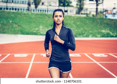 Indian woman running on track. Wearing long sleeve black top, black shorts with white stripe, pink runners. Long hair in pony tail. Looking into the lens. Multicultural, ethnic and inclusive theme.