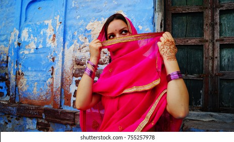 Indian woman in sari (saree) cover her face and look up. Old vintage wall and door on the background. Beautiful portrait of indian girl in traditional clothes.