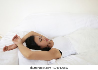 indian woman sleeping in the bed. pretty indian brunette real woman in bed smiling white sheets tann skin close up.