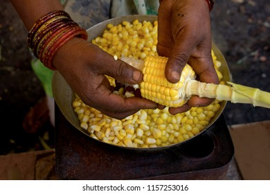 An Indian woman taking corn off the cob
