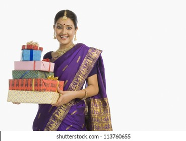 Indian woman in traditional Assamese dress holding gifts and smiling