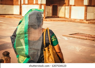 Indian woman in traditional dress walking in the outdoor. View form Back.
