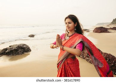 Indian woman in traditional saree clothes praying on the nature with sunset on background