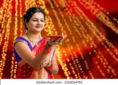 Indian woman in traditional sari and holding oil lamp in Hand celebrating Diwali or deepavali, fesitval.