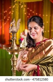 Indian woman in traditional wear saree lighting Diya Or Samai Lamp on ganesh festival or Diwali