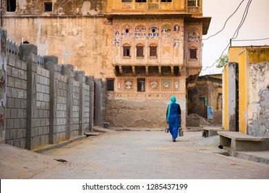 Indian woman walking on the street of Mandawa village, India