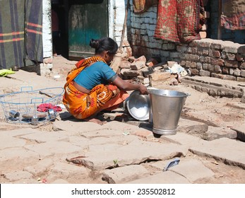 Indian woman washing dishes on the street