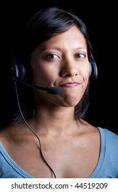 An Indian woman wearing a telephone headset and frowning