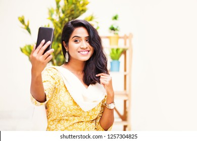 Indian woman wearing traditional suit taking selfie at home