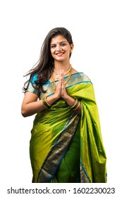 indian woman in welcome pose with both hands folded in  namaskara or prayer gesture, standing isolated over white background