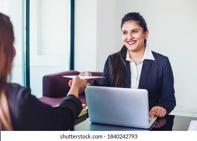 Indian woman working in a bank as a relationship manager issuing loan approval to the customer