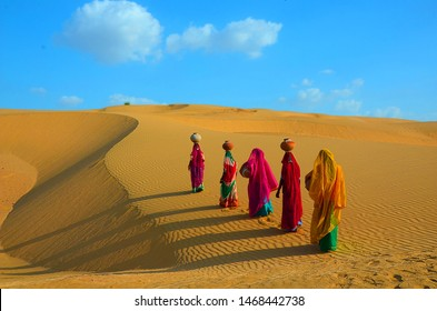 Indian women carrying heavy jugs of water on their head and walking on a yellow sand dune in the hot summer desert against blue sky.water crises, jaisalmer, rajasthan, india