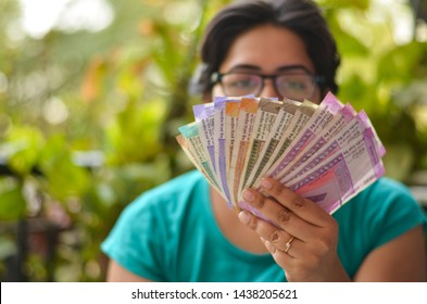 An Indian women holding all the colorful new released Indian Rupees currency notes after demonetisation in denominations 10,50,100, 200, 500, 2000 in her hands with her blur face in the background