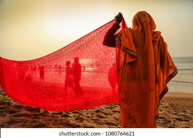Indian women pilgrims drying their colorful sarees under sun after taking holy bath at puri beach.
