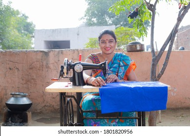 Indian women stitching cloths by machine at out side the home