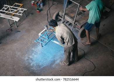 An Indian worker doing spray painting on Iron bars in a Factory. As on 13 Dec 2016, Kanpur, India.