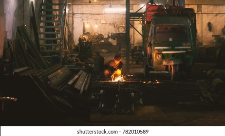 Indian workers are welding iron rods using welding mask in a Iron Factory. As on 13 Dec 2016, Kanpur, India.