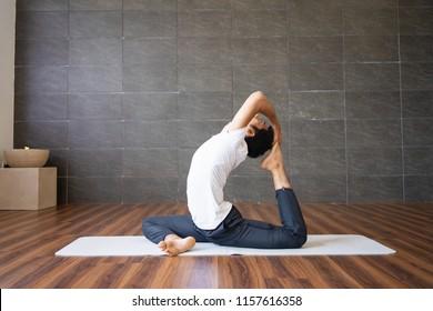 Indian yogi doing king pigeon yoga pose in gym. Man practicing advanced yoga. Yogi concept. Side view.