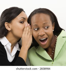 Indian young adult woman whispering in ear of mid-adult African-American woman.