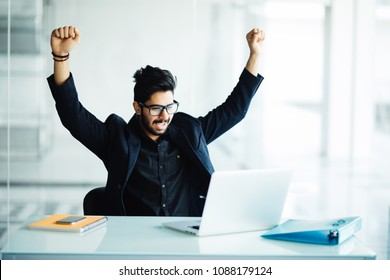 indian young bearded businessman with hands stretched pose while working on laptop, celebrating Victory