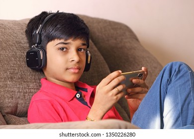 Indian young boy listen music with headphone and holding mobile phone