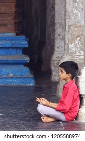 Indian young boy meditating at hindu temple