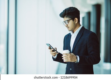 Indian young business man use phone while drink coffee in modern office