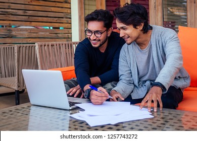 Indian young business people businessman freelancer working outdoors chaise lounge on the beach with laptop.two successful friends freelancing surfing remote work summer vacation in tropical paradise.