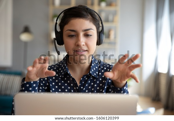 Indian young business woman student teacher tutor wear wireless headset video conference calling on laptop computer talk by webcam learn teach in online chat, distance webinar online teaching concept