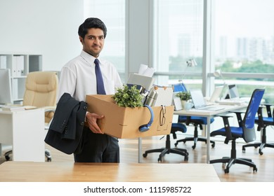 Indian young businessmann with box moving to a new workplace