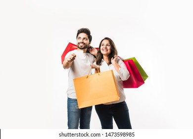 Indian young couple shopping bags and blank debit/credit or electronic card for payment, standing isolated over white background. selective focus