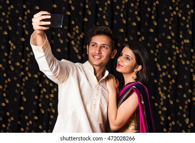 indian young Couple taking a self portrait or selfie using smart-phone in diwali festival over black background having bokeh of lighting series