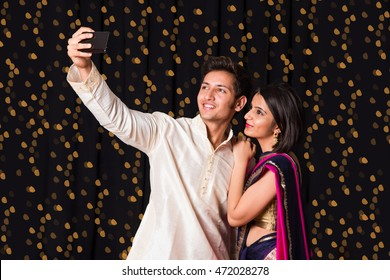 indian young Couple taking a self portrait or selfie picture using smart-phone on diwali festival over black background having bokeh of lighting series