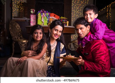 Indian young family celebrating Diwali with Flower Rangoli, Gift boxes and Diyas