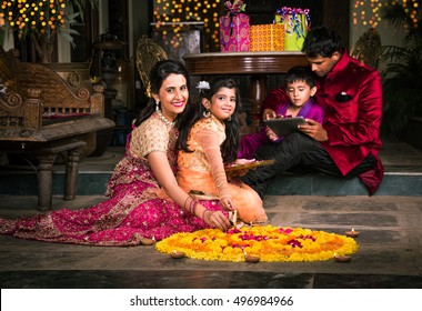 Indian young Family Making flower Rangoli or arranging diyas for diwali festival night at porch with gifts and bokeh in the background
